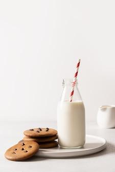 Melk voor de kerstman in fles en koekjes op wit.