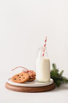 Melk voor de kerstman in fles en peperkoekkoekjes op witte achtergrond
