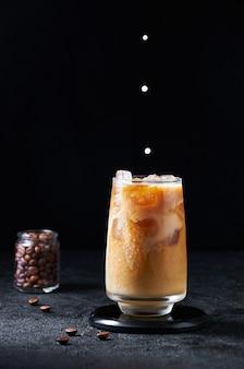 Melk wordt gegoten in ijskoffie in hoog glas op donkere achtergrond. concept verfrissend zomerdrankje.