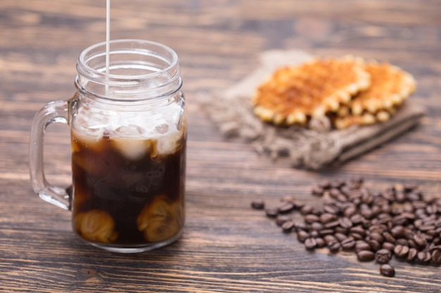 Melk wordt in de koffie gegoten. koffiebonen op de achtergrond