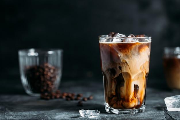 Melk wordt in ijskoffie op een donkere tafel gegoten