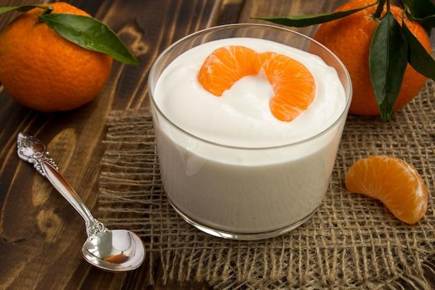 Melk yoghurt met mandarijn op de rustieke houten tafel