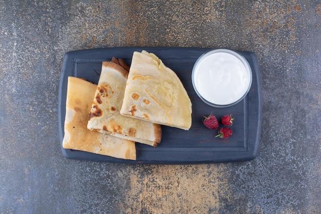 Melkachtige pannenkoeken met frambozen op een schotel