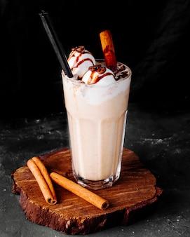 Melkachtige smoothie met ijsballetjes en kaneelstokjes.