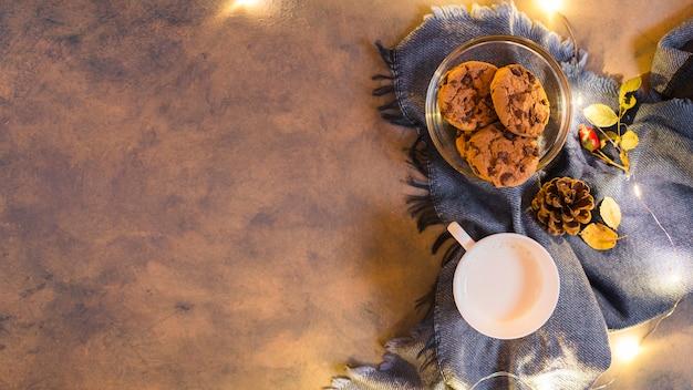 Melkbeker met koekjes op blauwe plaid