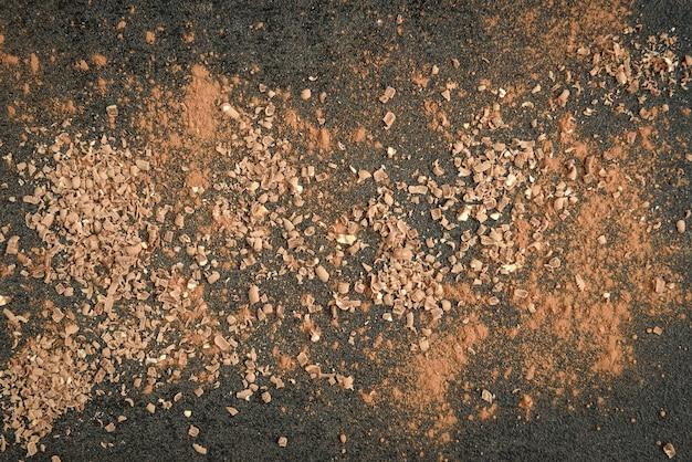 Melkchocolade reep chocoladeschilfers en cacao op zwarte ondergrond