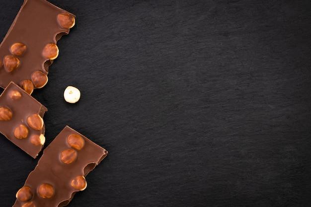 Melkchocoladestukjes met noten op een donkere achtergrond. bovenaanzicht met kopie ruimte.