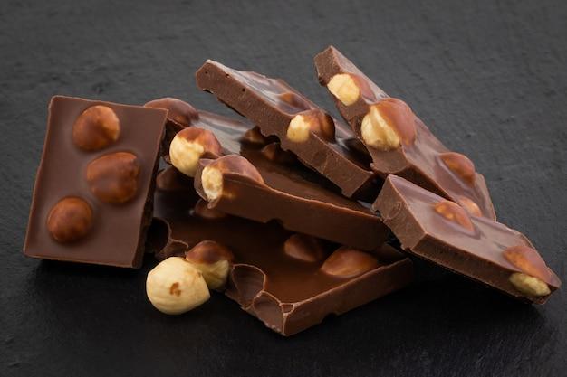Melkchocoladestukjes met noten op een donkere achtergrond.