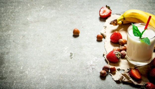 Melkdessert met noten, bessen en bananen. op de stenen tafel.