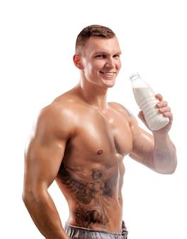Melkfles in de handen van sportpersoon, gezonde man. tatoeëren