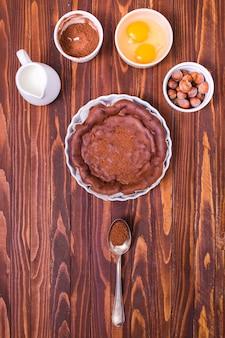 Melkkan; chocolade koffie poeder; eigeel en hazelnoot voor het maken van verse cake op houten oppervlak