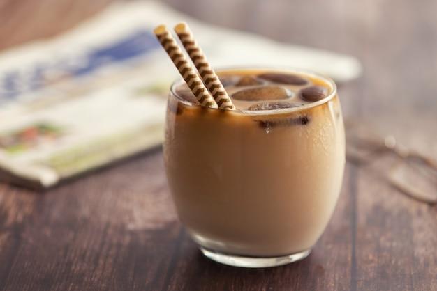 Melkkoffie cocktail in glas met bevroren koffieblokjes op houten tafel. zijaanzicht