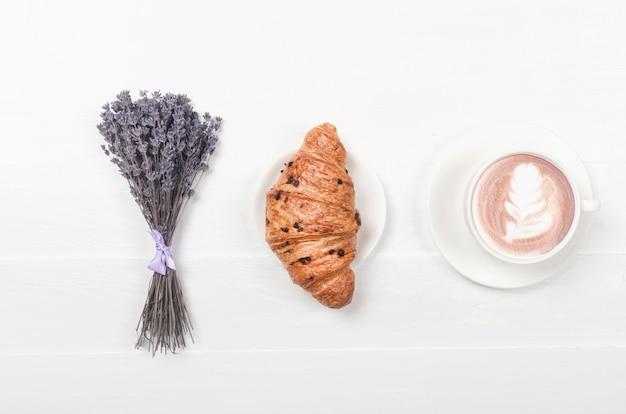 Melkkoffie met croissant op witte houten tafel en gedroogde violette lavendelbloem. bovenaanzicht