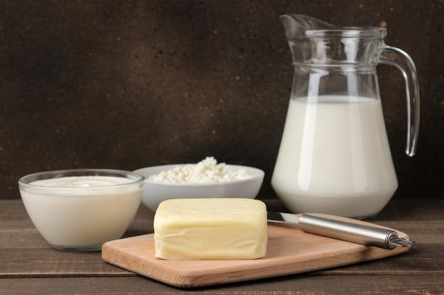 Melkproducten. melk, zure room, kaas, boter en kwark op een bruin houten tafel. ruimte voor tekst