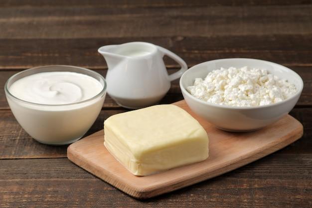 Melkproducten. melk, zure room, kaas, boter en kwark op een bruine houten tafel