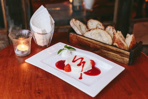 Melkpudding geserveerd met aardbeiensaus, slagroom.