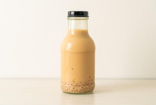 Melkthee met puddinggelei in glazen fles op tafel