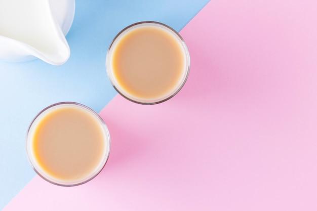 Melkthee op een roze-blauwe achtergrond. turkse theekopjes en melkkannetje. kopje traditionele engelse zwarte thee met melk. kopieer ruimte. bovenaanzicht