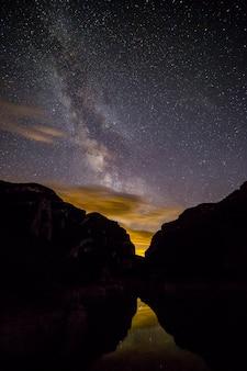 Melkweg bekijken 's nachts tussen de bergen