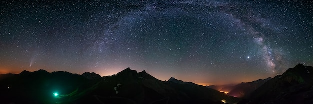 Melkweg boog en sterren in de nachtelijke hemel boven de alpen