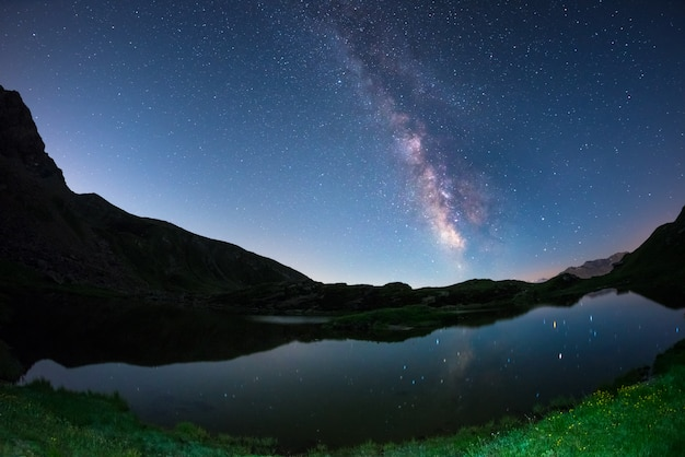 Melkweg boog en sterrenhemel weerspiegeld op meer op grote hoogte op de alpen