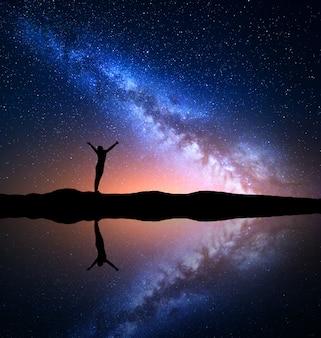 Melkweg en silhouet van een gelukkige vrouw op berg