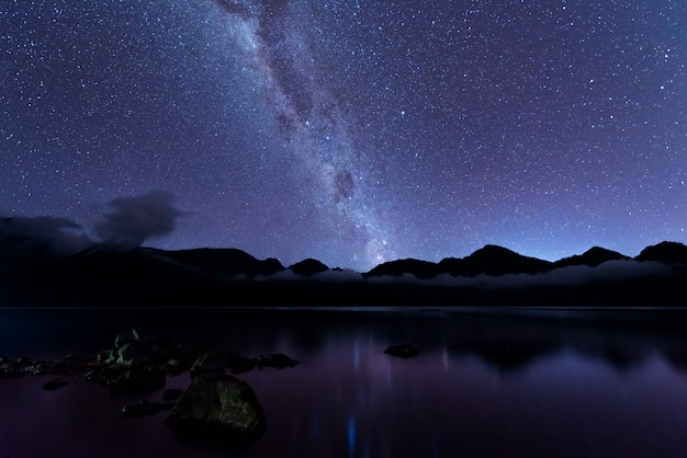 Melkweg landschap. duidelijk melkweg boven het meer segara anak in de krater van de berg rinjani aan de nachtelijke hemel. het eiland van lombok, indonesië.