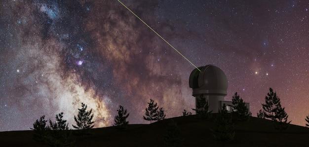 Melkweg met grote telescoop aan de horizon en pijnbomen in silhouet en groene laser die naar oneindig wijst
