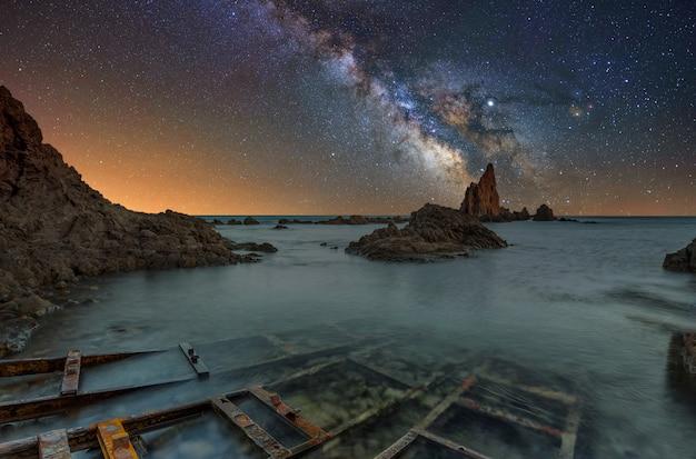 Melkweg over een rif in de middellandse zee in spanje, arrecife de las sirenas.