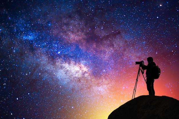 Melkweg, ster, silhouet gelukkig camera man op de berg met detail van de melkweg