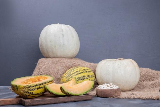 Meloen en pompoen op een houten bord op marmer.