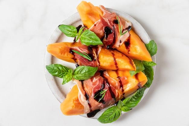Meloen meloen plakjes met prosciutto ham, balsamico azijn saus en basilicum in een bord op witte achtergrond. italiaans voorgerecht. bovenaanzicht. gezond eten