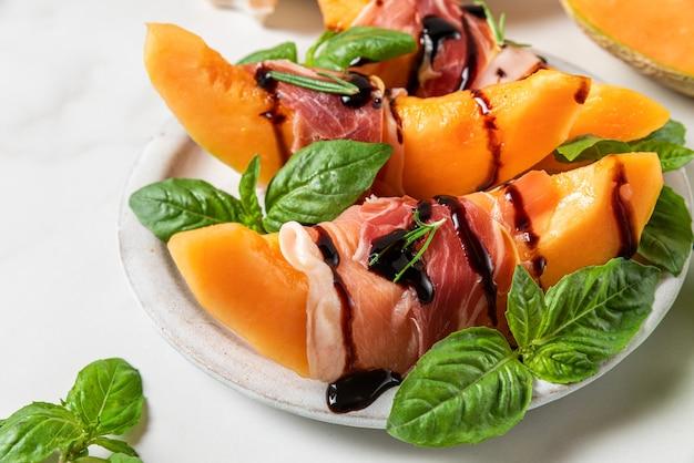 Meloen meloen plakjes met prosciutto ham, balsamico azijn saus en basilicum in een bord op witte achtergrond. italiaans voorgerecht. detailopname. gezond eten
