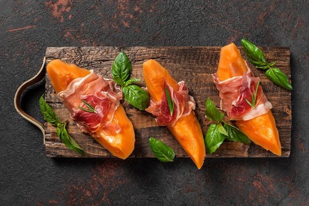 Meloen meloen plakjes met prosciutto ham en basilicum op zwarte achtergrond. italiaans voorgerecht. bovenaanzicht. gezond eten