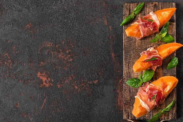 Meloen meloen plakjes met prosciutto ham en basilicum op zwarte achtergrond. italiaans voorgerecht. bovenaanzicht met kopie ruimte. gezond eten