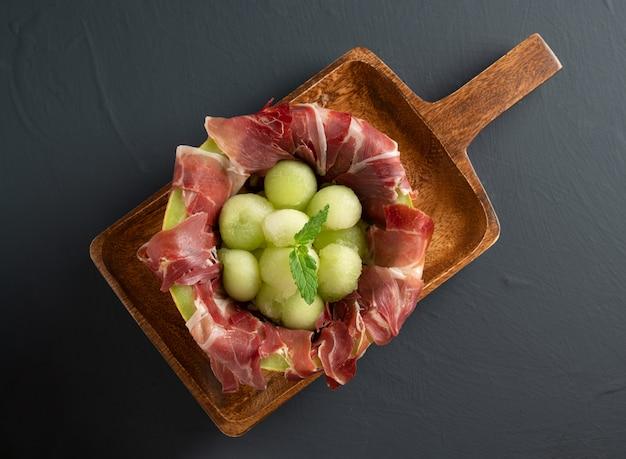 Meloen met ham op houten serveerplank