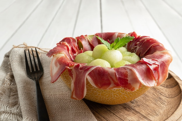 Meloen met luchtgedroogde ham, geserveerd in gehalveerde meloen gevuld met serranoham en meloenballetjes. detailopname
