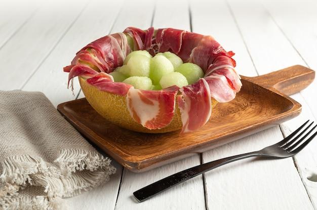 Meloen met luchtgedroogde ham, geserveerd in gehalveerde meloen gevuld met serranoham en meloenballetjes. kopieer ruimte