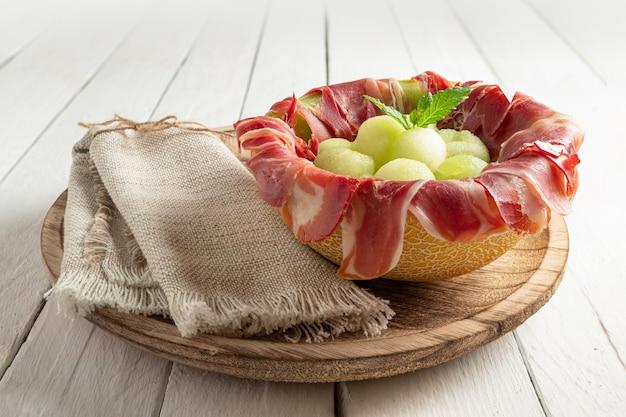 Meloen met luchtgedroogde ham, geserveerd in gehalveerde meloen gevuld met serranoham en meloenballetjes. op witte houten tafel