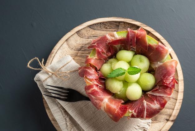 Meloen met luchtgedroogde ham, rustiek oppervlak met kopie ruimte. bovenaanzicht