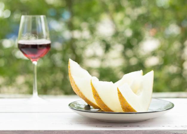 Meloen plakjes op een witte houten tafel, groene bomen op de achtergrond. een glas rode wijn.