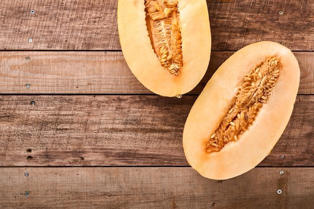 Meloen. stukjes verse meloen voor het maken van fruitdessert in glas op een oude houten achtergrond. bespotten. bovenaanzicht.
