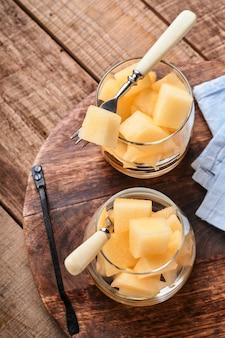 Meloen. stukjes verse meloen voor het maken van fruitdessert in glas op een oude houten ondergrond. bespotten. bovenaanzicht.