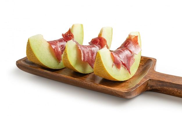 Meloenplakken met luchtgedroogde ham op houten dienende raad, die van de witte achtergrond wordt geïsoleerd