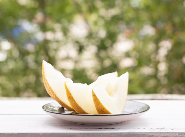 Meloenschijfjes op een witte houten tafel, groene bomen op de achtergrond. gezond eten.