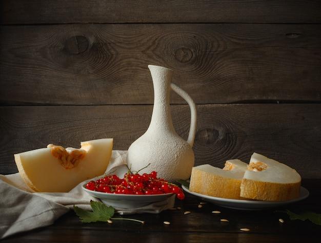 Meloenschijfjes op tafel, kruik, houten achtergrond