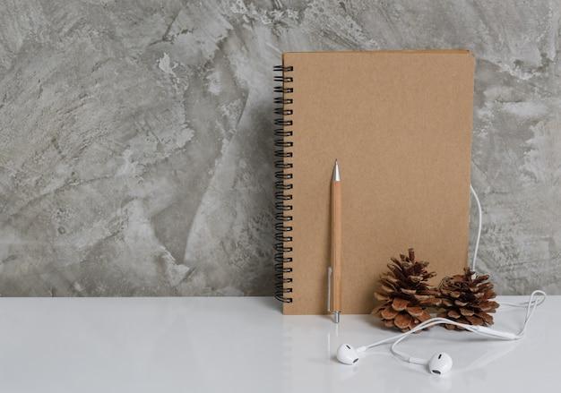 Memo notebook, potlood, dennenappel en oortelefoon op witte kunst tafelachtergrond, werkruimte concept