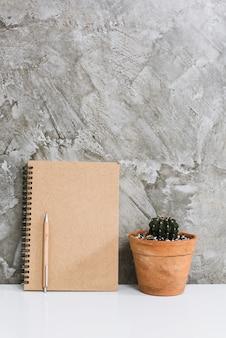 Memoblok, potlood, cactus in bloempot op witte bureau concrete achtergrond, werkruimteconcept