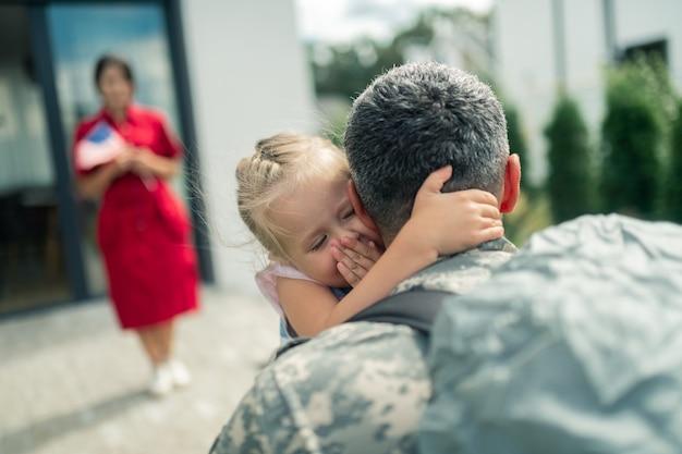 Memorabel en ontroerend. blonde dochter voelt zich gedenkwaardig en ontroerend terwijl ze eindelijk papa knuffelt