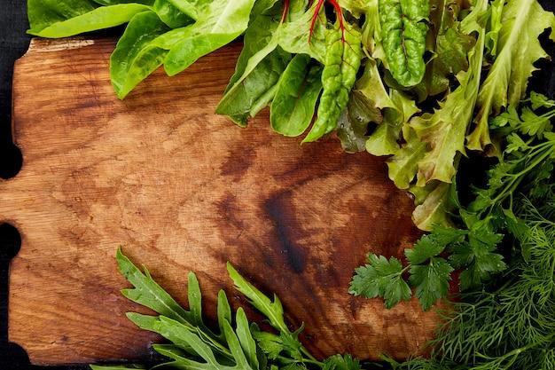 Meng de bladsalade op een houten snijplank.